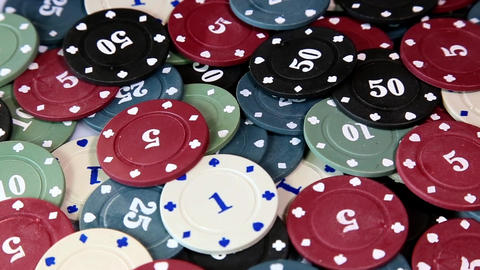 gambling, fortune, game and entertainment concept - poker chips on rotating surface close up Live Action