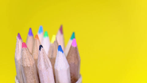 Closeup set of colored wooden pencils in different colors rotating on yellow background Live Action