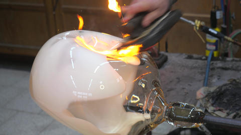 Master glassmaker heats a fire torch glass ball on a glass pipe. Hand shaping glass Live Action