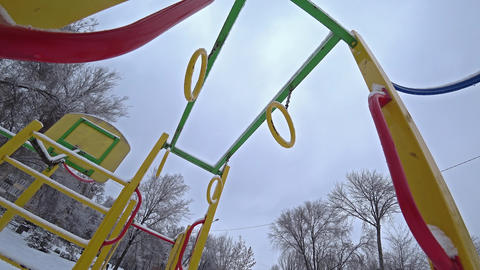 Empty children swings on a playground in city park at sunny winter day, view from the bottom Live Action