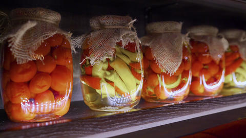 Jars of pickles are on the shelves. Jars of vegetables on the shelf. Stocks of Live Action