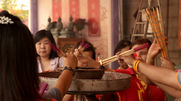 Thai People Lighting Incense Sticks at a Temple Stock Video Footage