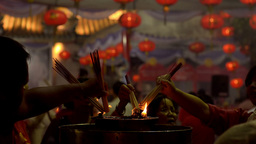 People Lighting Incense Sticks at a Temple at Night Footage