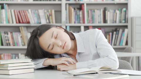 Tired female student falling asleep while studying Live Action