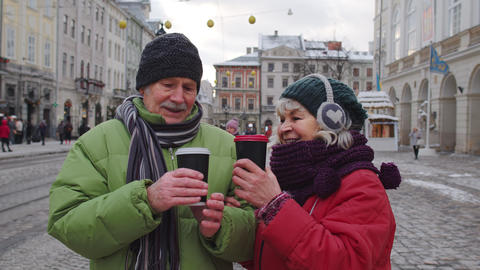 Senior old couple tourists grandmother grandfather traveling, drinking hot drink Live Action