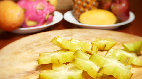 exotic fruits on the table. 4k , A carambola cut into pieces rotates on a Live Action