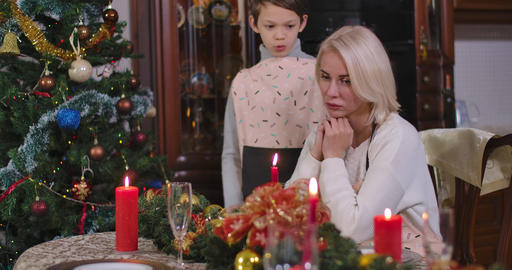 Cute Caucasian boy cheering up sad woman sitting at decorated Christmas table at Live Action