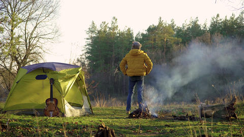 A cheerful man dances near a tent and a campfire in the woods Live Action