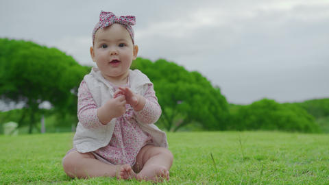 Portrait of cute baby girl infant todlder girl outdoors eating blade of grass Live Action
