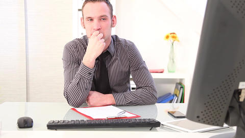 Businessman sits pensively in front of a computer Footage