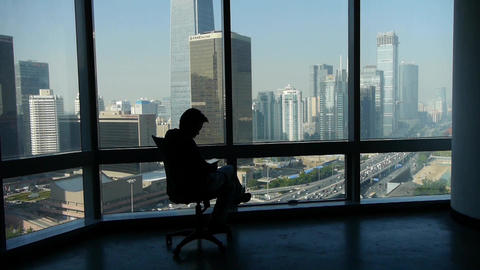 a business human sitting & reading,business building from french window Animation