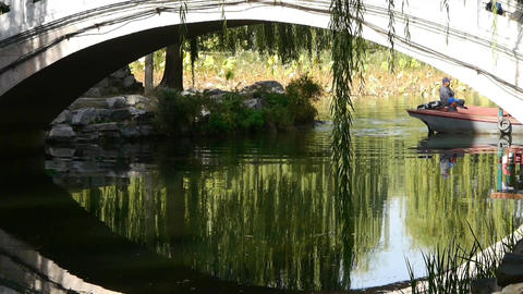 Arch bridge on lake & boat in Yuanmingyuan Park Beijing Stock Video Footage