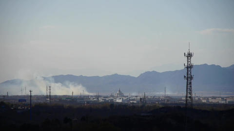 Panoramic of city town & factory smoke relying on mountains,Tower on hill Footage