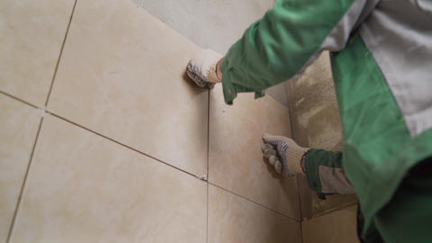 Master in overalls puts ceramic tiles on the wall. The master puts tiles in the Live Action
