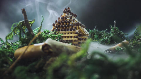scene with small house of matches among stubs in smoke Live Action