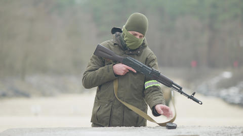 Confident Caucasian masked soldier attaching magazine to rifled gun and walking Live Action