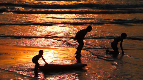 Children Playing on the Beach at Sunset Footage
