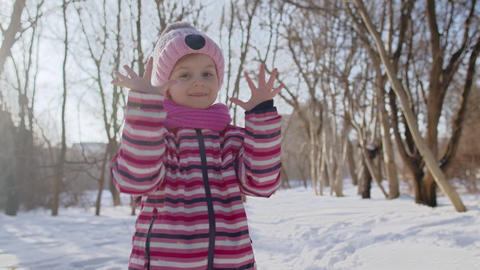 Smiling child kid showing ok sign, smiling, dancing, thumbs up on snowy road in Live Action