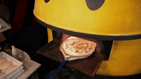 Overhead view of putting fresh fruit pizza in a warm oven. Putting fruit pizza Live Action