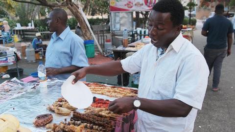 Forodhani Food Stalls, An African Seller Advertises his Food Market Zanzibar Live Action