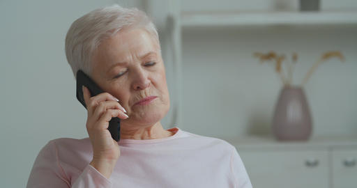 Elderly woman gray-haired lady old grandmother speaks on mobile phone to Live Action