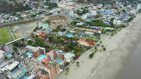 Aerial view of a small village alongside the beach, showing high and small buildings with many palm Live Action