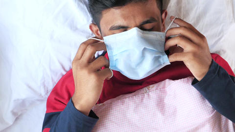 top view of sick men putting surgical face mask sleeping on bed Live Action