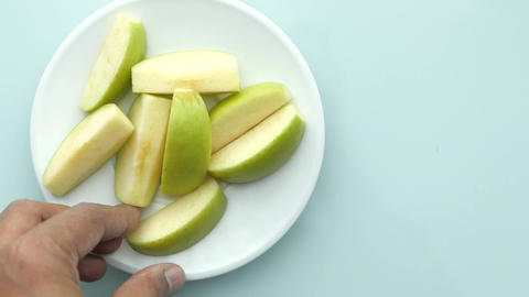 hand pick slice of green apple on light green background background Live Action