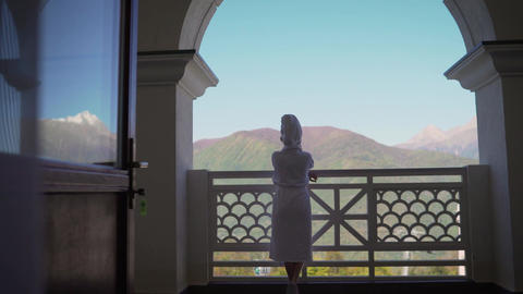 A girl in a white coat goes to the balcony. Back view. Girl on the big balcony Live Action