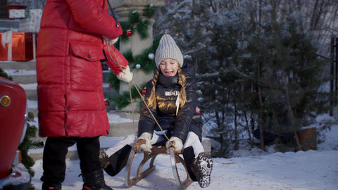 Playful girl sledding with friend on winter holidays. Teenagers girl having fun Live Action
