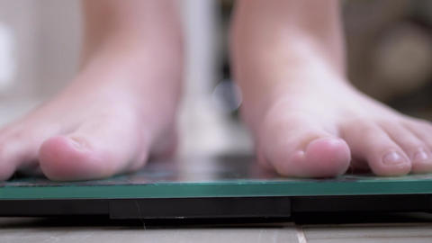 Teenage Child On Scales Measure Weight. Child Checks His Weight Barefoot. 4K Live Action