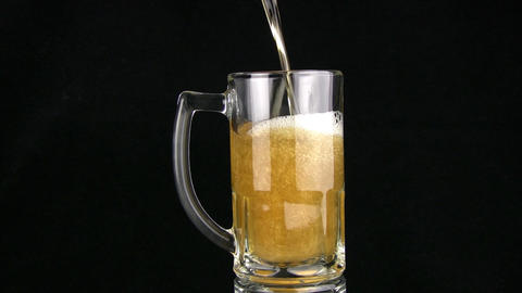 The beer is poured in a mug. Black background Footage