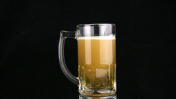 The beer is poured in a mug. Black background Stock Video Footage