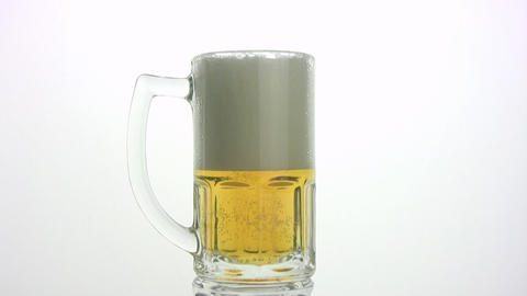The beer foam is poured through edge of mug. White... Stock Video Footage