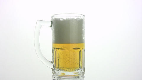 The beer foam is poured through edge of mug. White background Footage