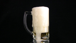 The beer foam is poured through edge of mug. Black... Stock Video Footage