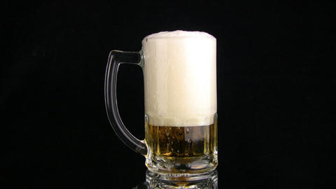 The beer foam is poured through edge of mug. Black background Footage