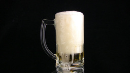 The beer is poured slow through edge of mug Stock Video Footage