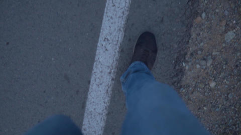 Feet in black shoes walking by the side of the road POV, concept of freedom and Live Action