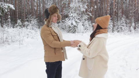 a guy gives a girl a gift in a snowy winter forest a happy girl jumps for joy Live Action