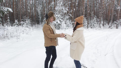 a guy makes a surprise gift to a girl in a snowy winter forest. a happy girl and Live Action