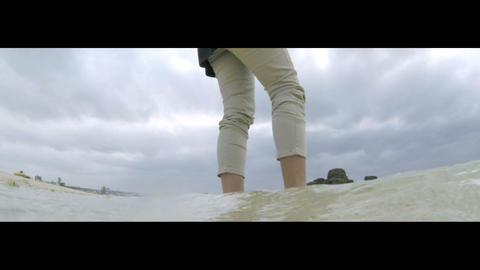 曇り空の海辺で波を受ける女性 stock footage