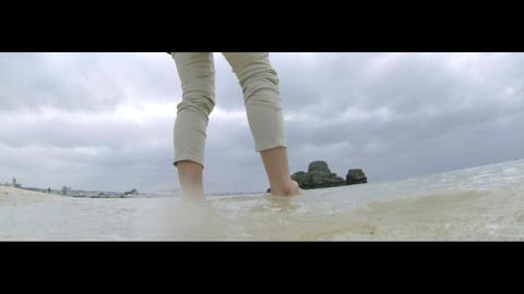 曇り空の海辺で波を受ける女性 Stock Video Footage