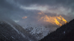 Time Lapse of cloudy morning by a snow mountain with Sun Light in the morning Footage