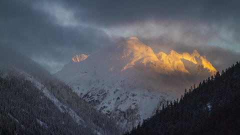 Time Lapse of cloudy morning by a snow mountain with Sun... Stock Video Footage