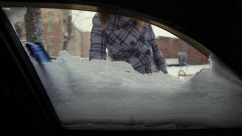 Car in snow, woman cleans snow from car Stock Video Footage