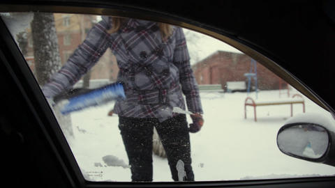 Car in snow, woman cleans snow from car Footage