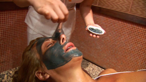 Woman puts a mud face mask b Footage