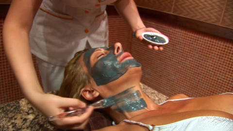 Woman puts a mud face mask b Stock Video Footage