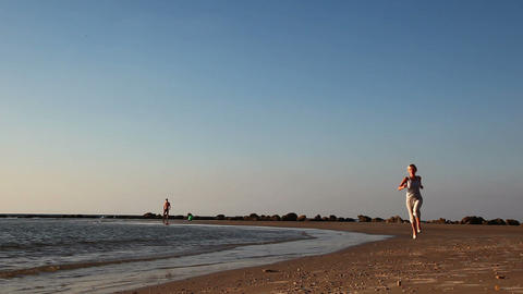 Girl jogging along a Beach Stock Video Footage